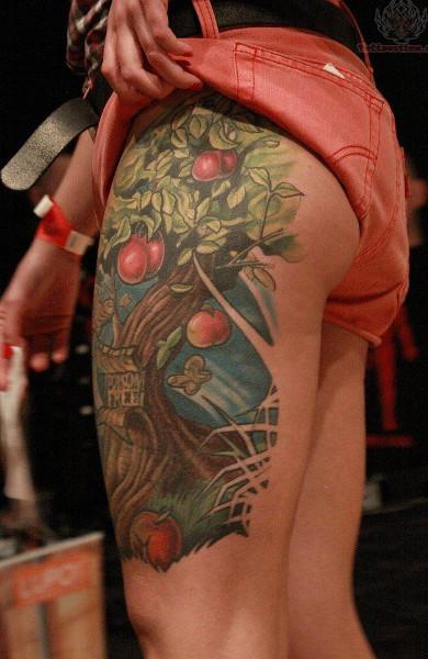 Татуировка яблоня на бедре
