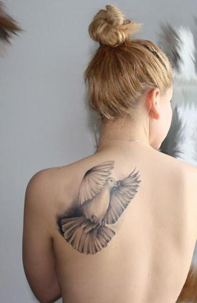 Татуировка голубь на спине девушки